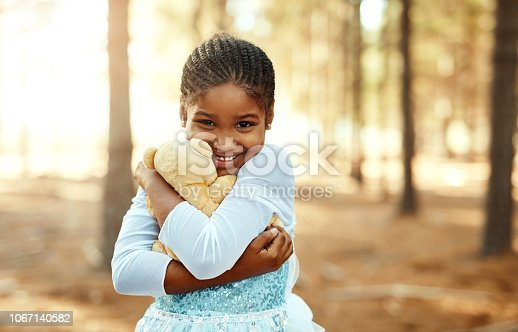 Portrait of a little girl playing in the woods with her teddybear