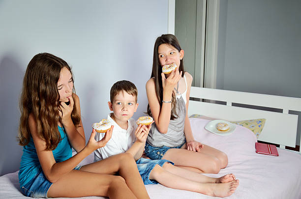 kids are sitting in bed and eating donuts - little girls giving head stock photos and pictures
