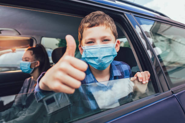 Kids are travelling in car during coronavirus outbreak stock photo