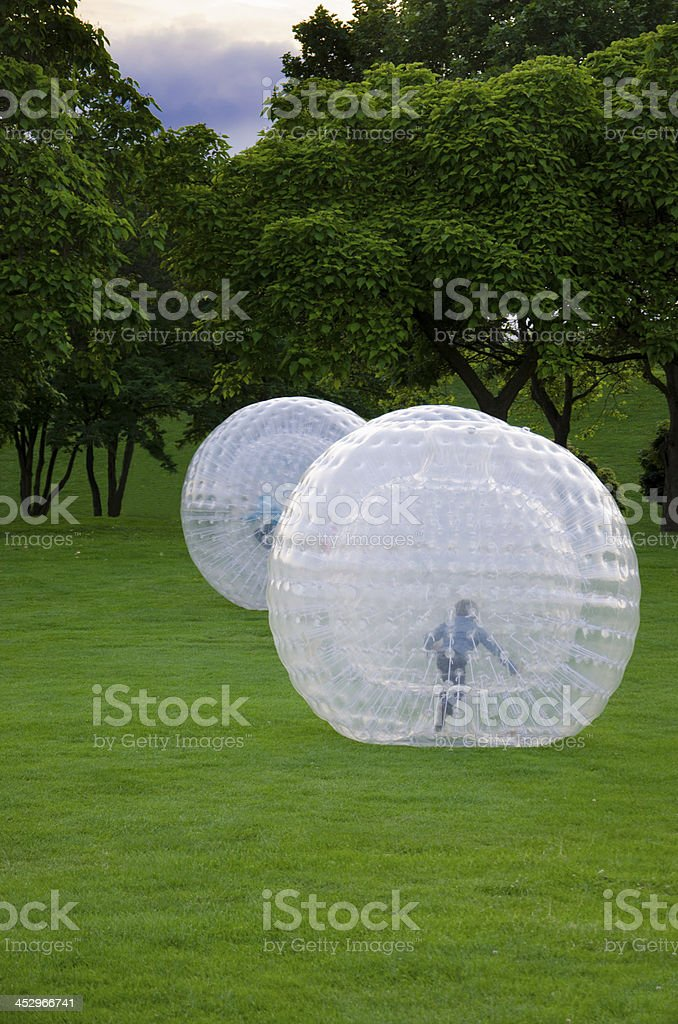 Kids are Zorbing in a Park stock photo