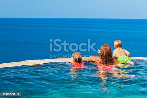 883117662 istock photo Kids at edge of infinity swimming pool with sea view. 1205533186