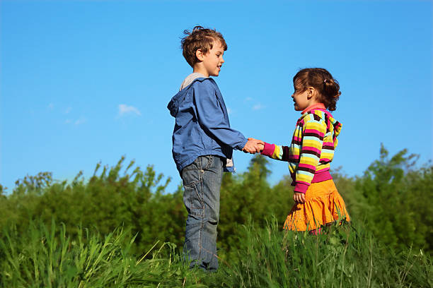Kids at green meadow holding hands stock photo