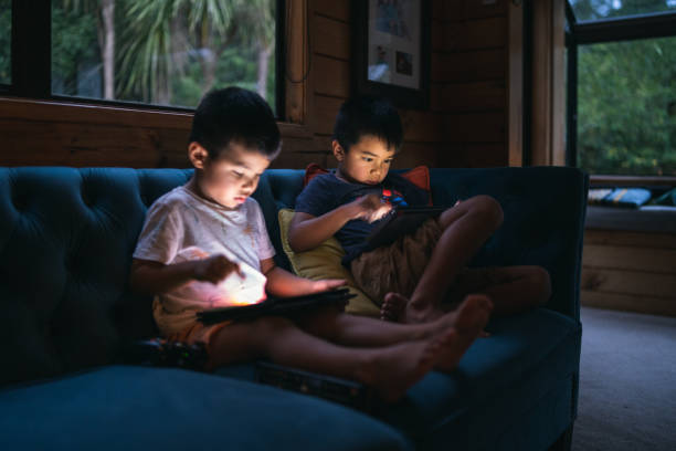 Kids at home using smart device. stock photo