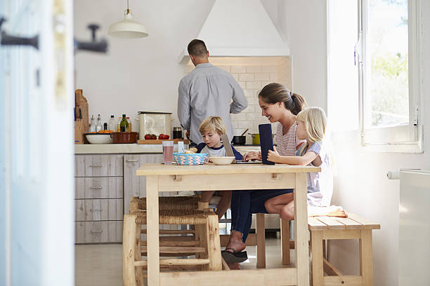 Kids at kitchen table with mum, dad cooks, view from - Photo