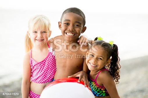 A multi-ethnic group of children at the beach in their swimsuits playing with a beach ball.
