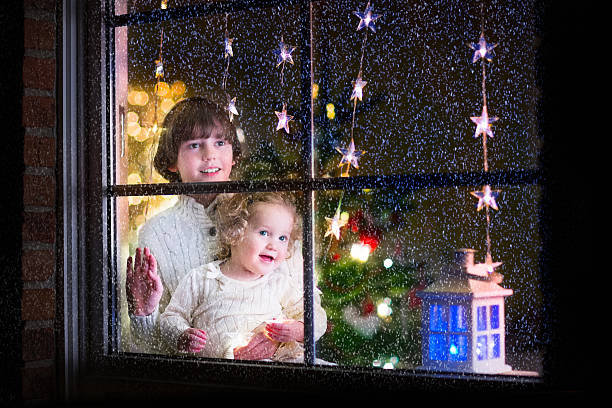 Kids at window on Christmas eve Two happy children, little curly toddler girl and laughing boy in warm knitted winter sweaters standing next to a window in a decorated living room with Christmas tree, view from outside of the house boy looking out window stock pictures, royalty-free photos & images