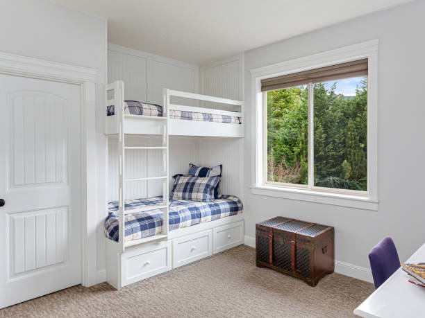 kid's bedroom in new luxury home with built-in bunk beds, colorful bedding, chest, desk, and large window stock photo