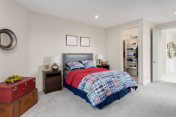 kid's bedroom in new luxury home with colorful bedding, chest, toys, and walk-in closet stock photo