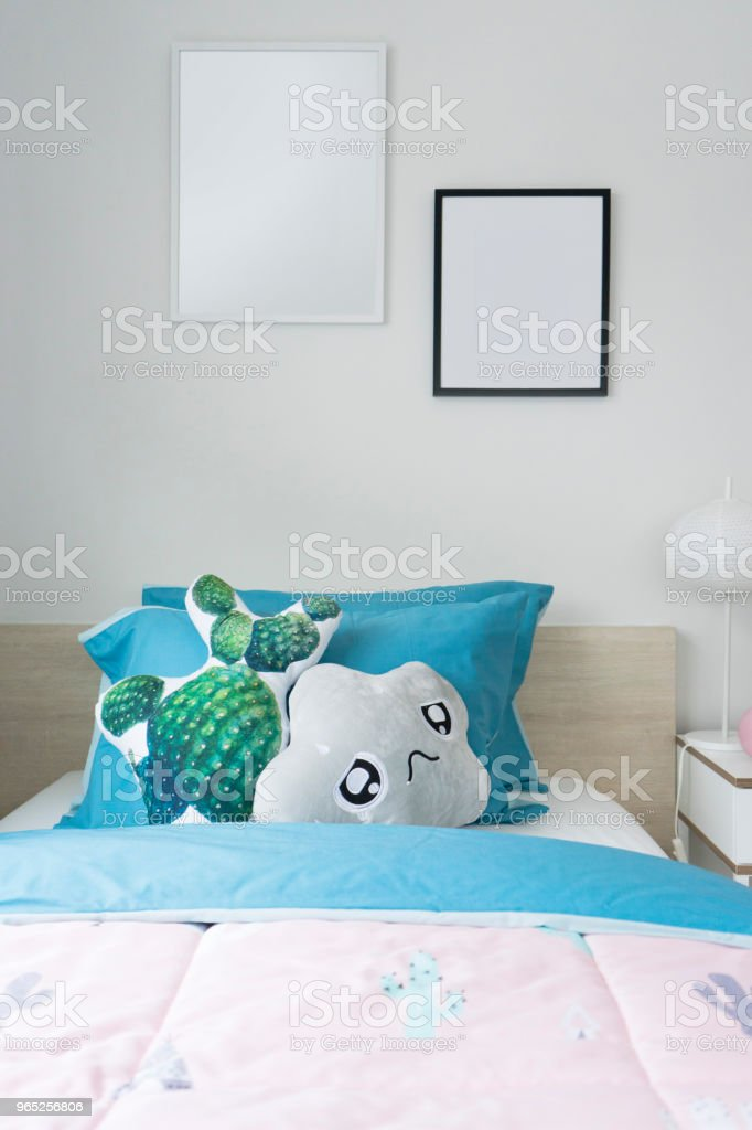 kid's bedroom with doll and blue blanket and pillow on bed. zbiór zdjęć royalty-free