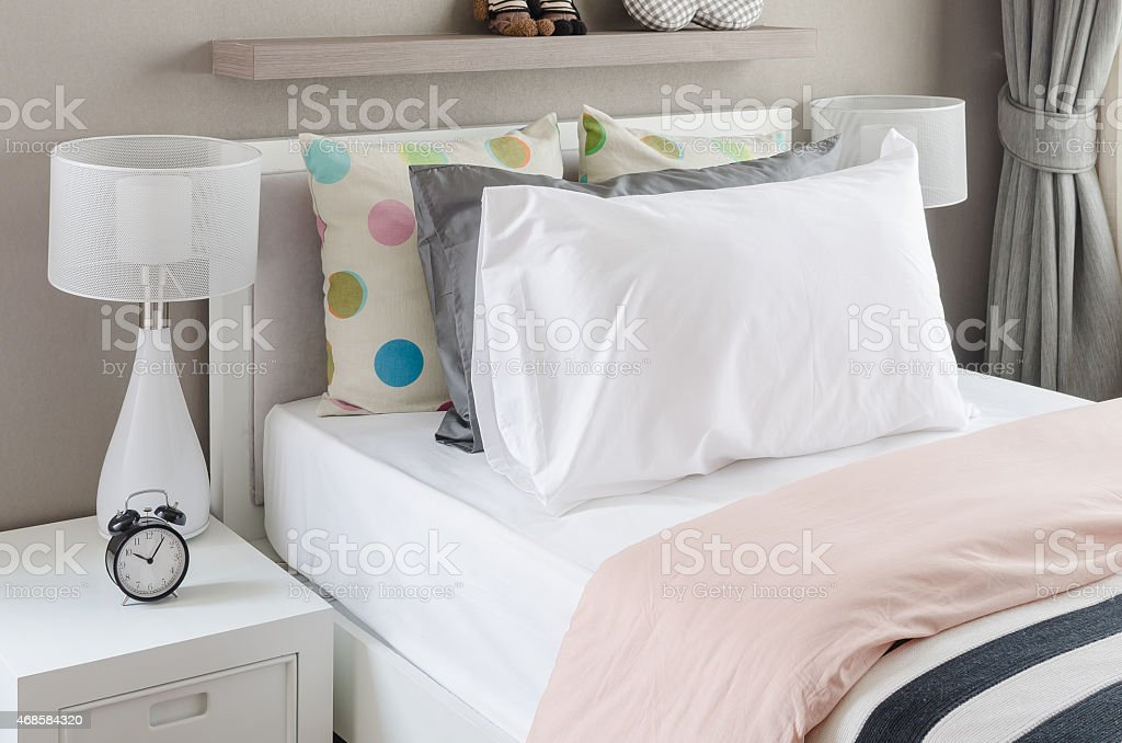 kid's bedroom with white pillows and lamp on modern bed stock photo
