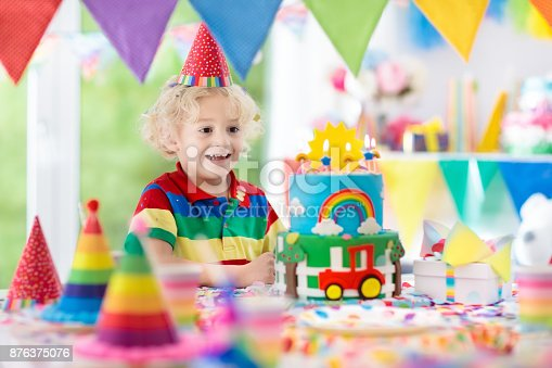 istock Kids birthday party. Child blowing out cake candle 876375076