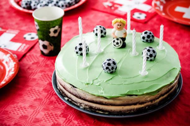kinder geburtstag party fußballthema. schokoladenkuchen wie fußballplatz mit sieben kerzen geschmückt. - einladungskarten kindergeburtstag stock-fotos und bilder