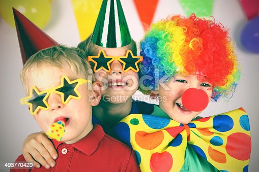Three boys dressed up in colorful party clothing are celebrating a birthday. One child is wearing a colorful clown wig, a red nose, and a giant bow tie, the other two boys have party hats and funny sunglasses on, one of them is blowing a party blower. This is a tinted, retro style image of the childrens party.