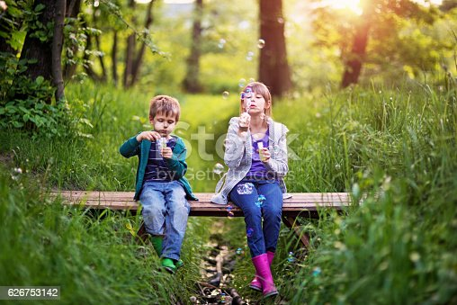 618034312 istock photo Kids blowing bubbles on the bridge in the springtime 626753142