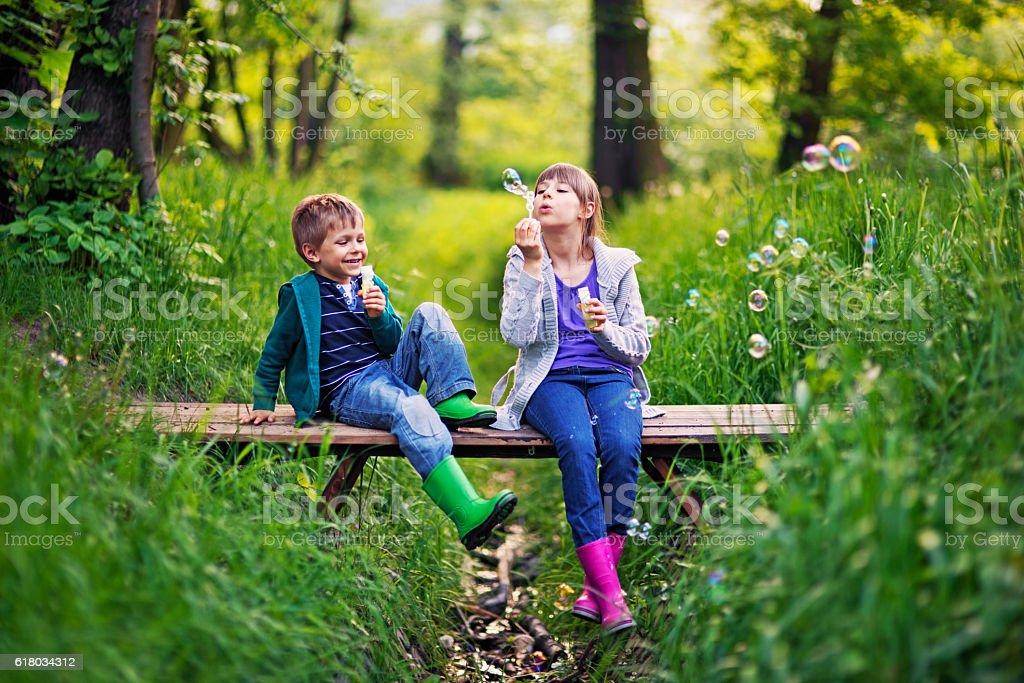 Kids blowing  bubbles on the bridge stock photo