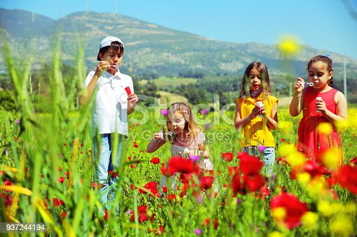 618034312 istock photo Kids blowing bubbles on the field 937244194