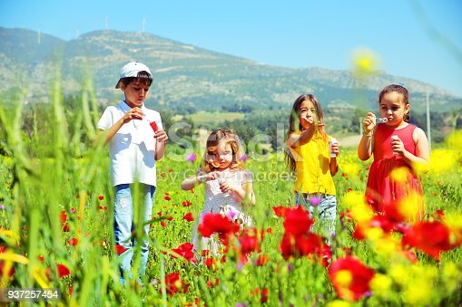 618034312 istock photo Kids blowing bubbles on the field 937257454