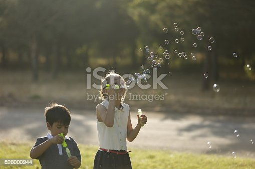 618034312 istock photo Kids blowing bubbles 826000944