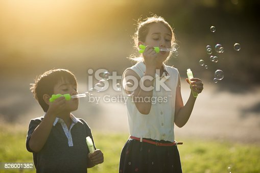 618034312 istock photo Kids blowing bubbles 826001382
