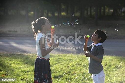 618034312 istock photo Kids blowing bubbles 826001524