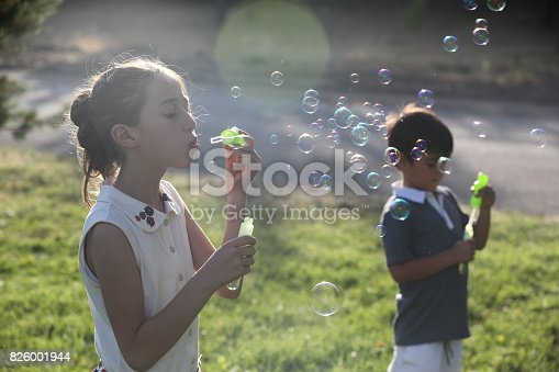 618034312 istock photo Kids blowing bubbles 826001944