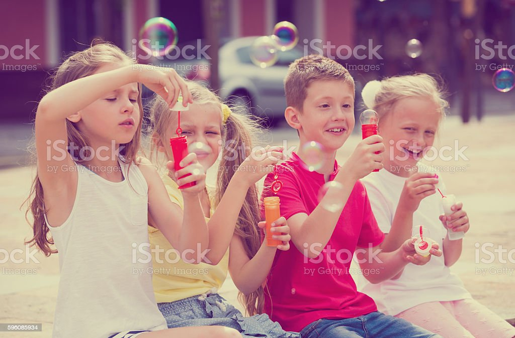 Kids blowing soap bubbles royalty-free stock photo