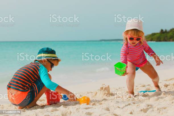 kids- boy and girl- play with sand on summer beach