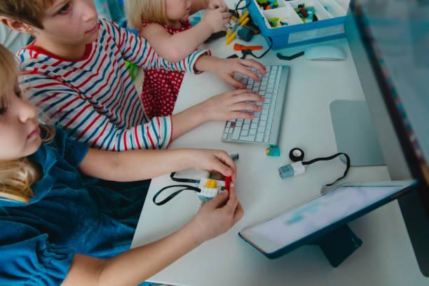 Kinder bauen Roboter und programmieren es mit Touchpad und Computer – Foto