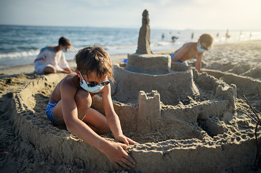 Three kids are having fun building a huge sandcastle on a beach on a sunny summer day.  COVID-19 pandemic and the kid are wearing surgical masks. Nikon D850