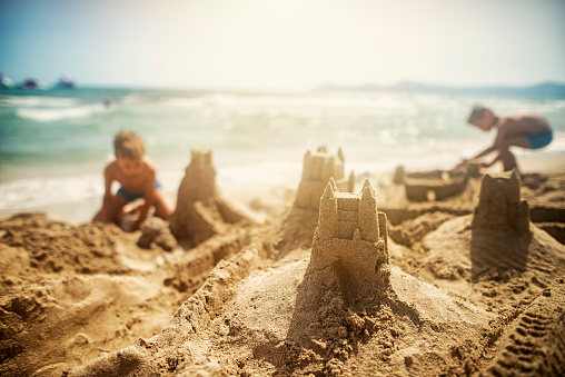 Two little brothers are building sandcastles. Sunny summer day.
