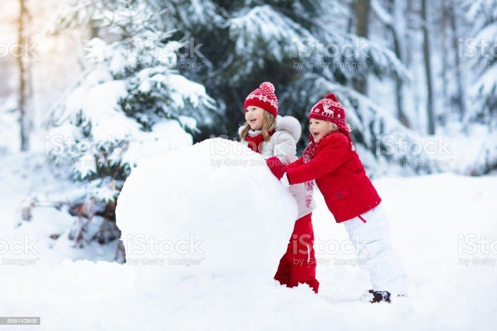 Crianças, construção de boneco de neve. Crianças na neve. Diversão de inverno. - foto de acervo