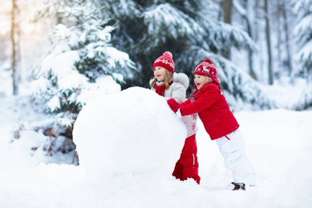 Kids building snowman. Children in snow. Winter fun. Children build snowman. Kids building snow man playing outdoors on sunny snowy winter day. Outdoor family fun on Christmas vacation. Boy and girl play snow balls. Winter clothing for baby and toddler. christmas fun stock pictures, royalty-free photos & images