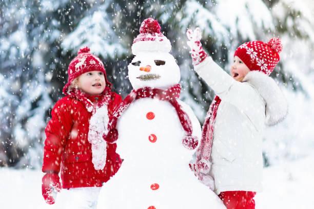 kinder schneemann bauen. kinder im schnee. winterspaß. - schneemann bauen stock-fotos und bilder