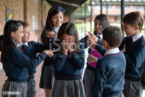 Group of kids bullying a girl at the school and laughing while pointing at her - education concepts