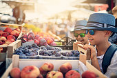 Kids buying at the street market in Verona, Italy. Brothers are browsing fresh organic fruit.\nNikon D850