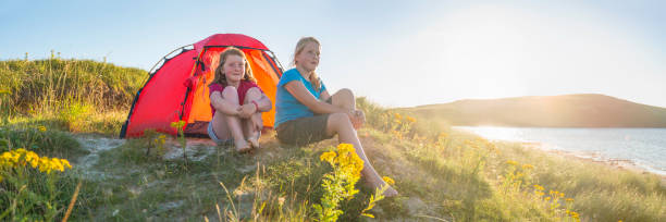 Kids camping idyllic golden beach dunes overlooking tranquil summer ocean stock photo