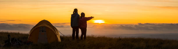 Kids camping on idyllic mountain top overlooking golden sunset panorama Young hikers standing beside their dome tent pitched high on a grassy mountain ridge looking over the clouds to the golden sunset beyond. image stock pictures, royalty-free photos & images