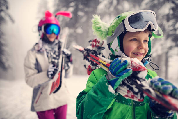 Kids carrying skis on a beautiful winter day Little boy and his siter are carrying skis. Kids are wearing funny ski helmets. Beautiful winter day.  ski resort stock pictures, royalty-free photos & images