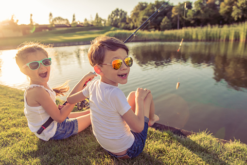 Funny stylish little boy and girl in sun glasses are looking at camera and smiling while catching fish in the pond using a fishing rod, sitting on the ground