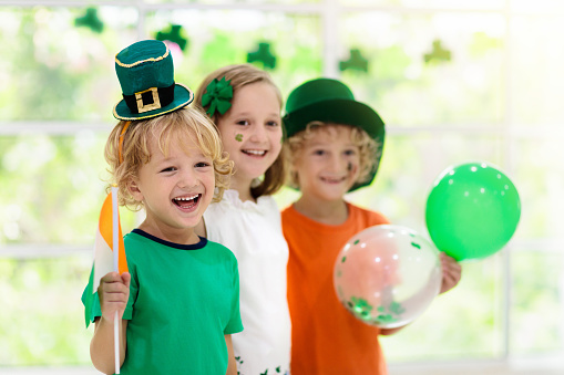 Family celebrating St. Patrick's Day. Irish holiday, culture and tradition. Kids wear green leprechaun hat and beard with Ireland flag and clover leaf. Children having fun at St Patrick party.