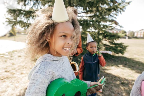 kinder feiern geburtstag im freien mit musikinstrumenten - probeessen spiele stock-fotos und bilder