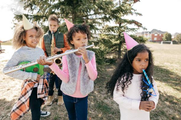 kinder feiern geburtstag im freien mit musikinstrumenten - musik kuchen stock-fotos und bilder