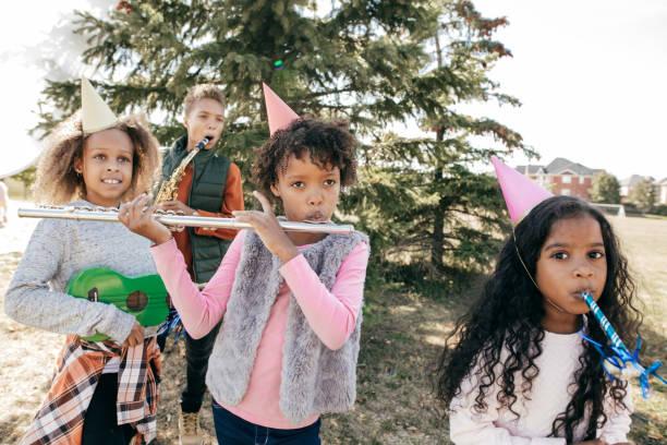 kinder feiern geburtstag im freien mit musikinstrumenten - vorschulgeburtstag stock-fotos und bilder