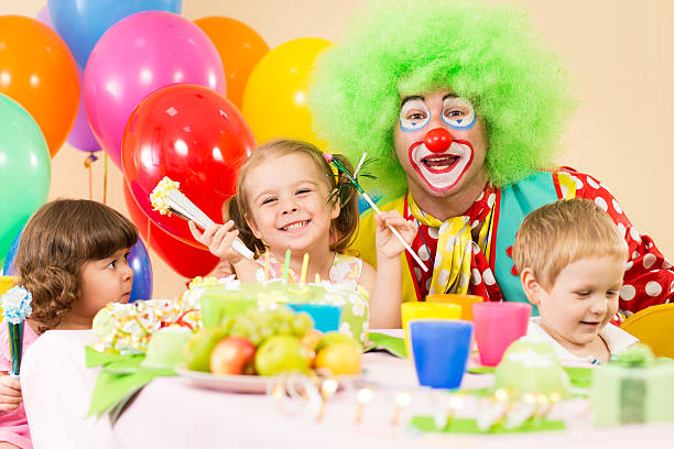 kids celebrating birthday party with clown stock photo
