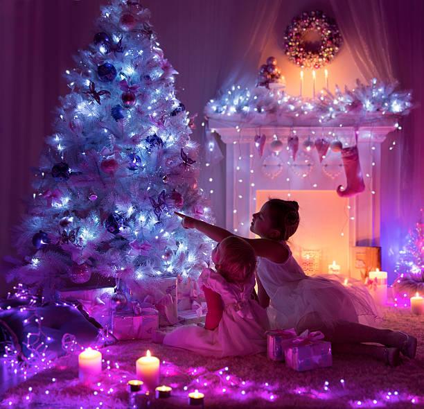 kids celebrating christmas, child baby, decorated xmas tree fireplace lights - lila mädchen zimmer stock-fotos und bilder