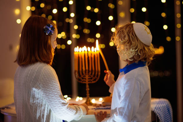 Kids celebrating Hanukkah. Festival of lights. Kids celebrating Hanukkah. Jewish festival of lights. Children lighting candles on traditional menorah. Boy in kippah with dreidel and Sufganiyah doughnut. Israel holiday. judaism stock pictures, royalty-free photos & images