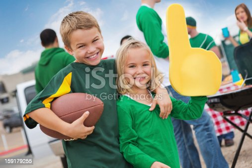 istock Kids cheering sports team during college football stadium tailgate party 159179255