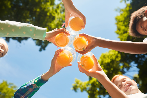 Low angle close up of kids holding glasses with orange juice against blue sky outdoors, copy space