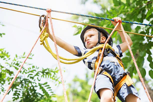 kids climbing in adventure park. - mini amusementpark stockfoto's en -beelden