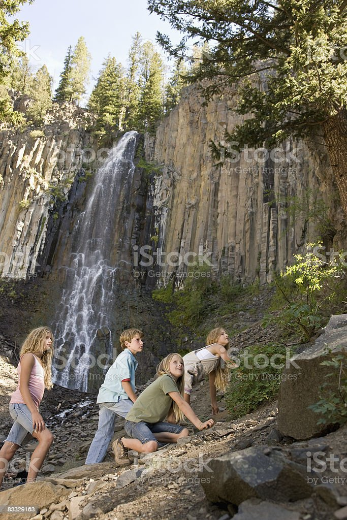 Kids climbing up mountain royaltyfri bildbanksbilder